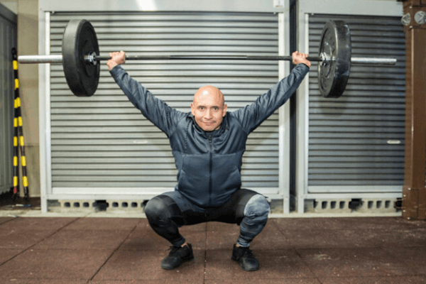 A flexible military man in a deep squat whilst holding a 40kg barbell above him