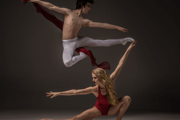 A man and woman ballet dancing and performing incredible stretches