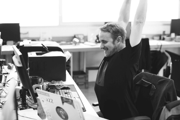 A man at his desk smiling whilst stretching up into the air above.