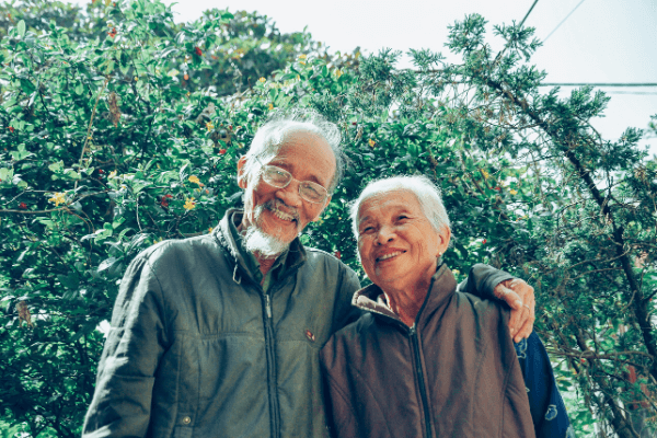 An elderly asian couply who are stress free, happy, and smiling in their garden.