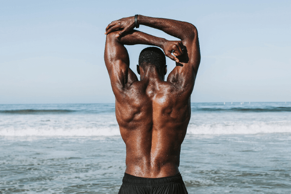A back of a strong black man stretching on the edge of the sea