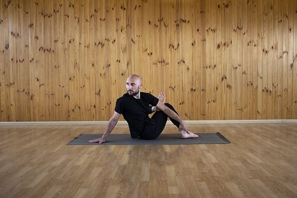 Yoga man stretching his glutes with a static stretch on the wooden floor