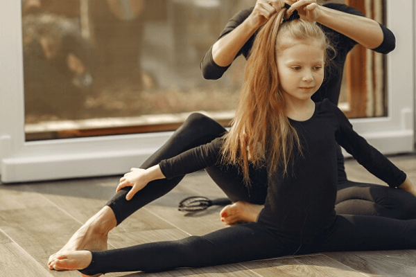 Young daughter doing the splits with her mother doing her hair from behind