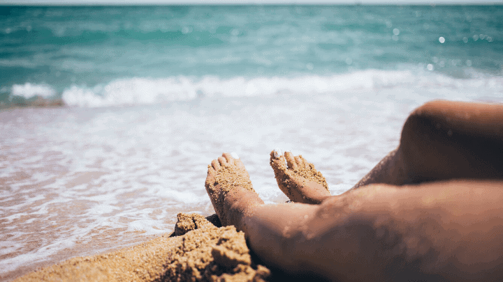 a photo of a lady's legs relaxing next to the ocean resembling the hero image of the article, 'how to lose leg fat fast'