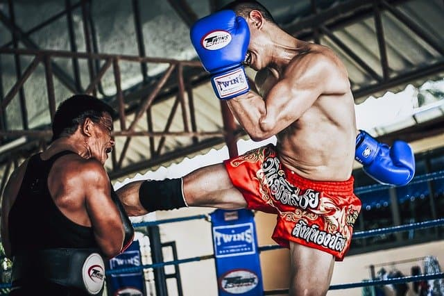 Muay Thai fighter with his hands up, mid-kick