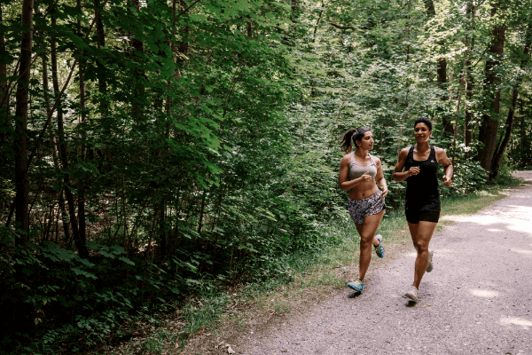 two female friends running on a sunny day, trying to lose some weight