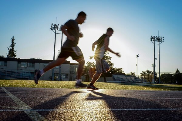 Two men from US Navy doing sprints on a running track with sun behind them.