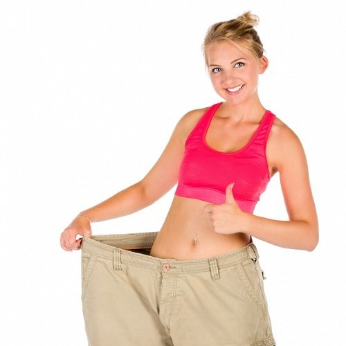 a young lady in oversized trousers with her thumbs up showing off her slim body