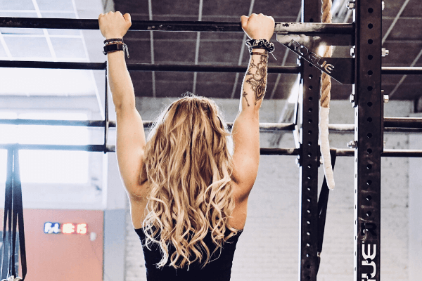 A blonde lady hanging from a rogue power rack