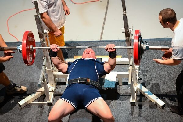 A strong man doing the bench press using a squat rack