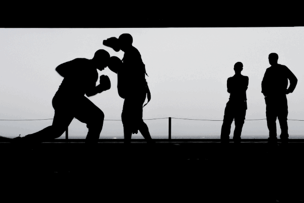boxer on mitt with coach in a black and white silhouette