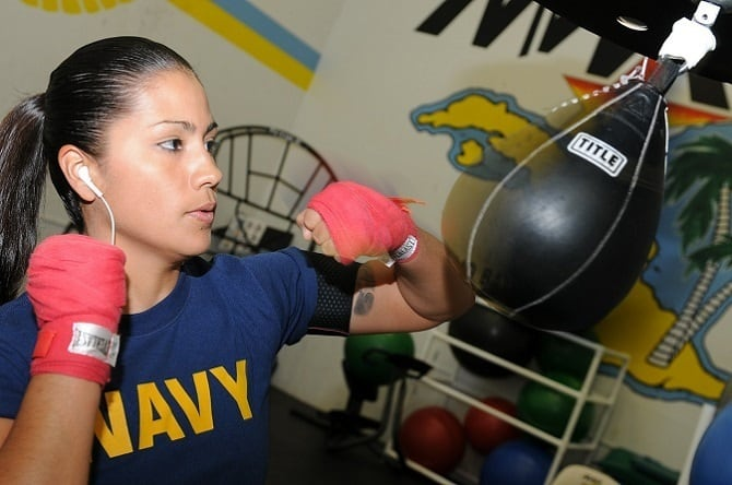 lady hitting speed bag and showing off her hand wraps