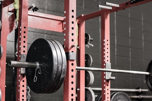 power rack in red colour, with a fully loaded barbell