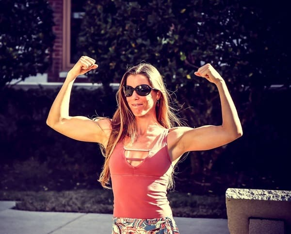 women with sunglasses showing off her muscles