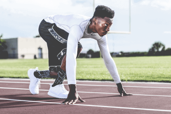 man getting ready to sprint on a running track