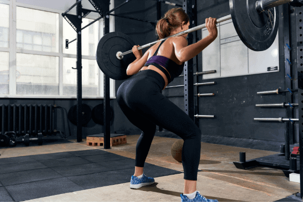 fit lady performing back squat in the gym