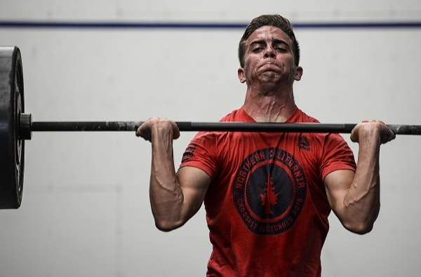 fit man in red shirt front squatting with explosiveness
