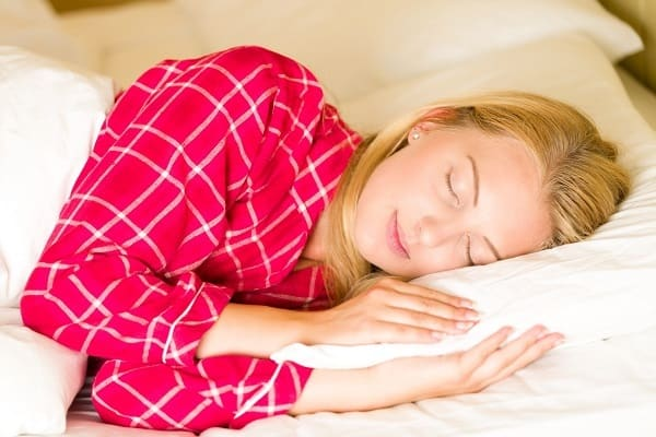 lady with pink pyjamas asleep in bed on her rest day