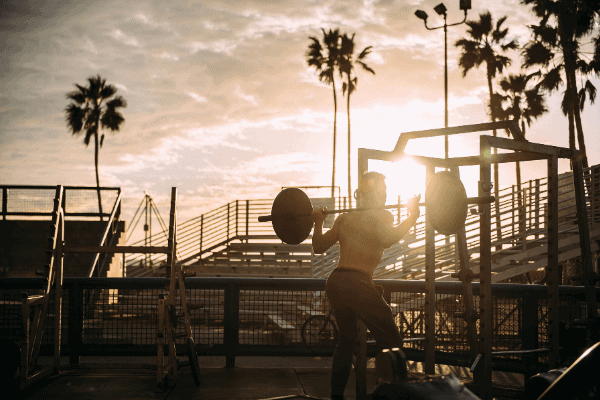 Man in outdoor gym with shirt off doing a back squat