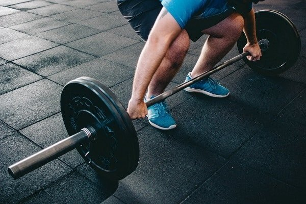 man with blue shirt and blue shoes about to perform deadlift