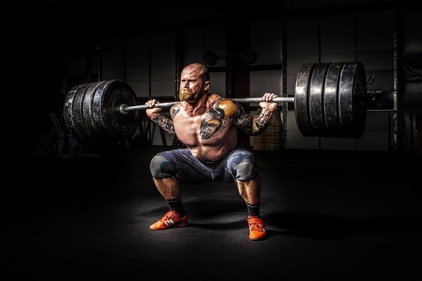 strong man back squatting heavy barbell as an example of intensity