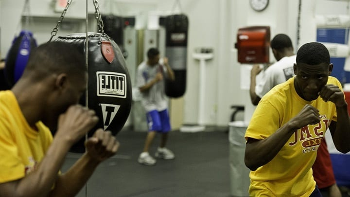 black fighter with yellow shirt shadow boxing in gym