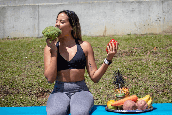 Lady with a fit body and strong core eating vegetables outside