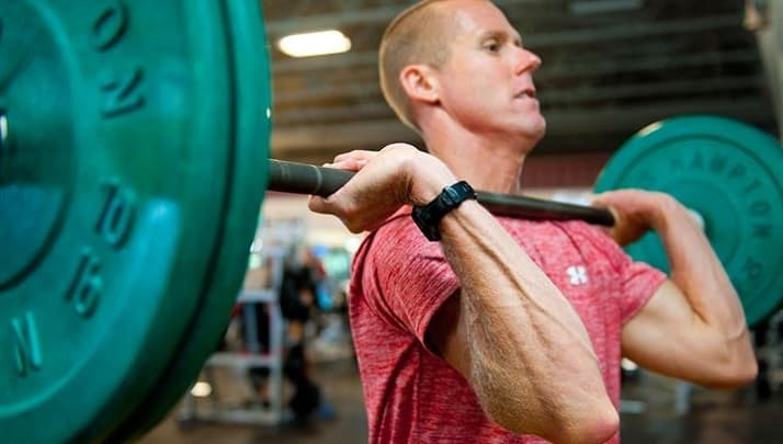 Man with a pink shirt performing heavy front squat resembling the disadvantages of squats