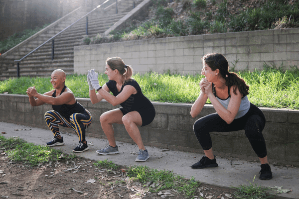 three ladies performing body weight squats together outdoors