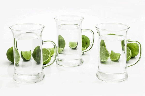 three large glasses of water with lime chunks in background