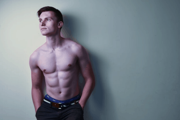 Young man posing shirtless showing off his strong core