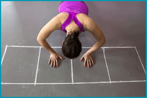 a lady ready kneeling ready to use a self made agility ladder she made with chalk.