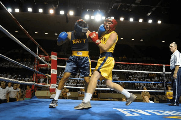 Two boxers in a stadium and one getting punched with his opponents left hook.
