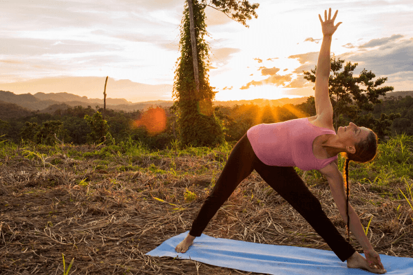 Parama K Williams performing a yoga pose with a mexican sunset in the background
