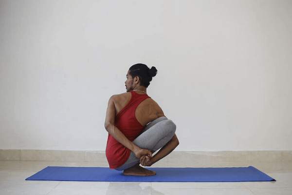 A black man with a red tank top in a complex twisting yoga pose