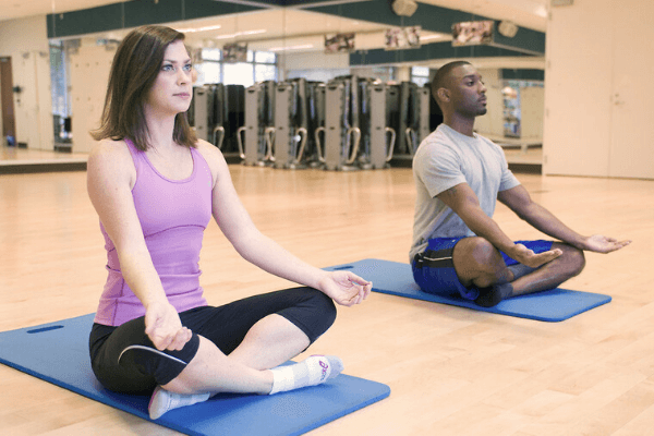 A man and woman cross legged performing yoga indoors.