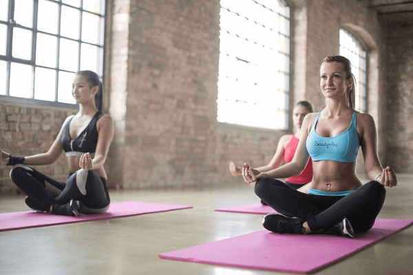 A yoga class of three women sitting on their pink mats in an indoor hall made from brick