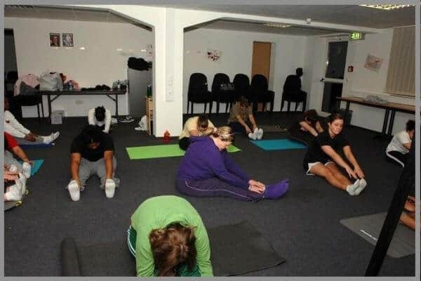 A class of yogis preparing for their yoga session