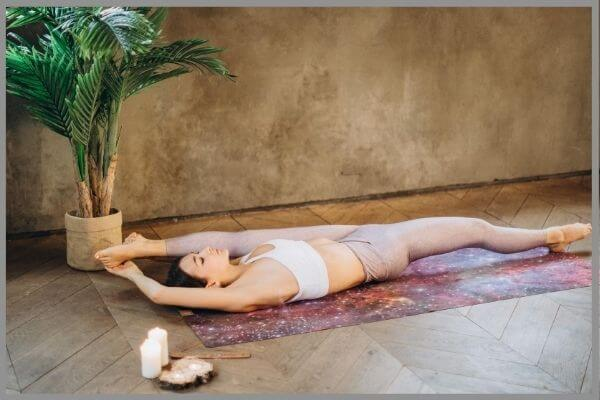 A yogi holding a yoga pose with a candle by her side.