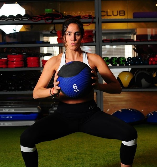 a fit lady squatting with a blue medicine ball