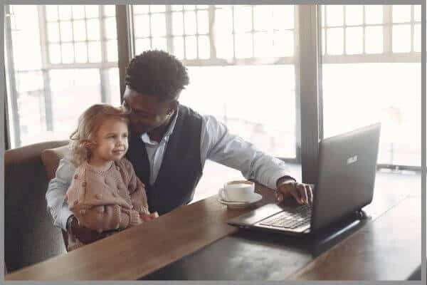 A man kissing his daughter's head whilst booking a yoga class online.