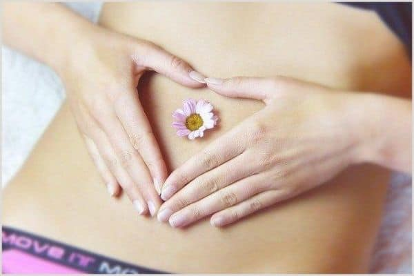A close up of a womans slim belly with a daisy in her belly button.