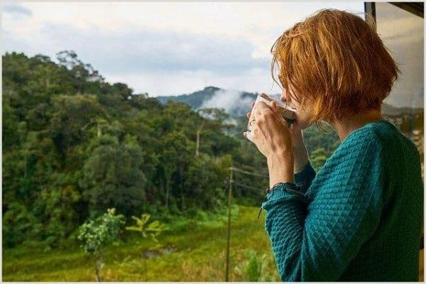 A ginger lady detoxing with a herbal drink in the morning surrounded by mountains.