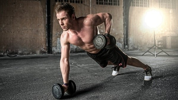 A strong man with his shirt off performing a one arm dumbbell row in mid repetition