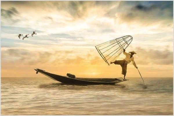 An Asian fisherman balancing on the side of a boat with one foot in the air.