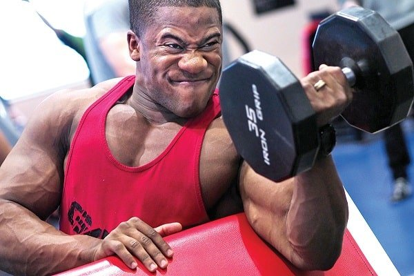 Body building champion performing one arm bicep curl at the gym