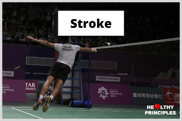 A professional badminton player in mid air, diving towards the net to return a net shot.