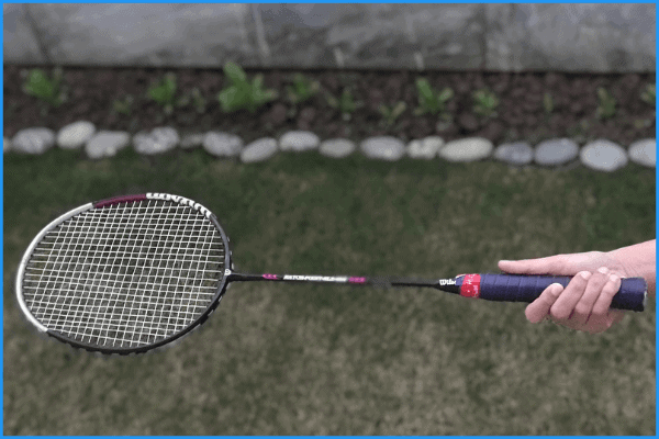 A badminton player demonstrating how to hold the panhandle grip with his racquet.