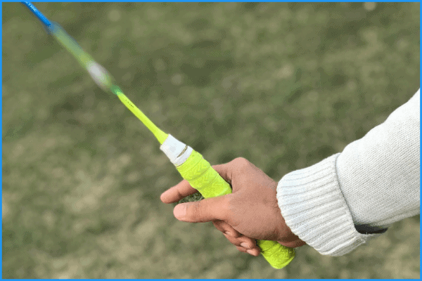 A badminton player demonstrating where to place your thumb to create the 'v,shape' in the forehand grip