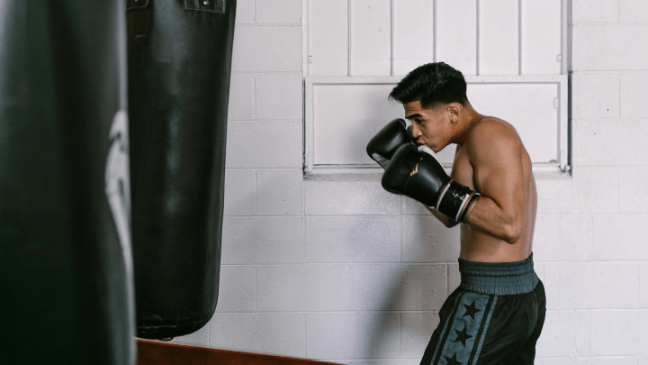 A young man throwing punches at a black heavy bag in a boxing gym.
